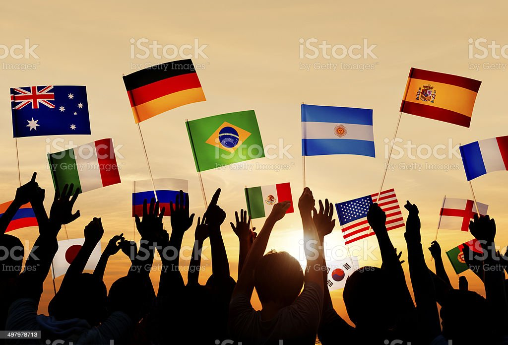 Silhouetted people holding various country flags stock photo