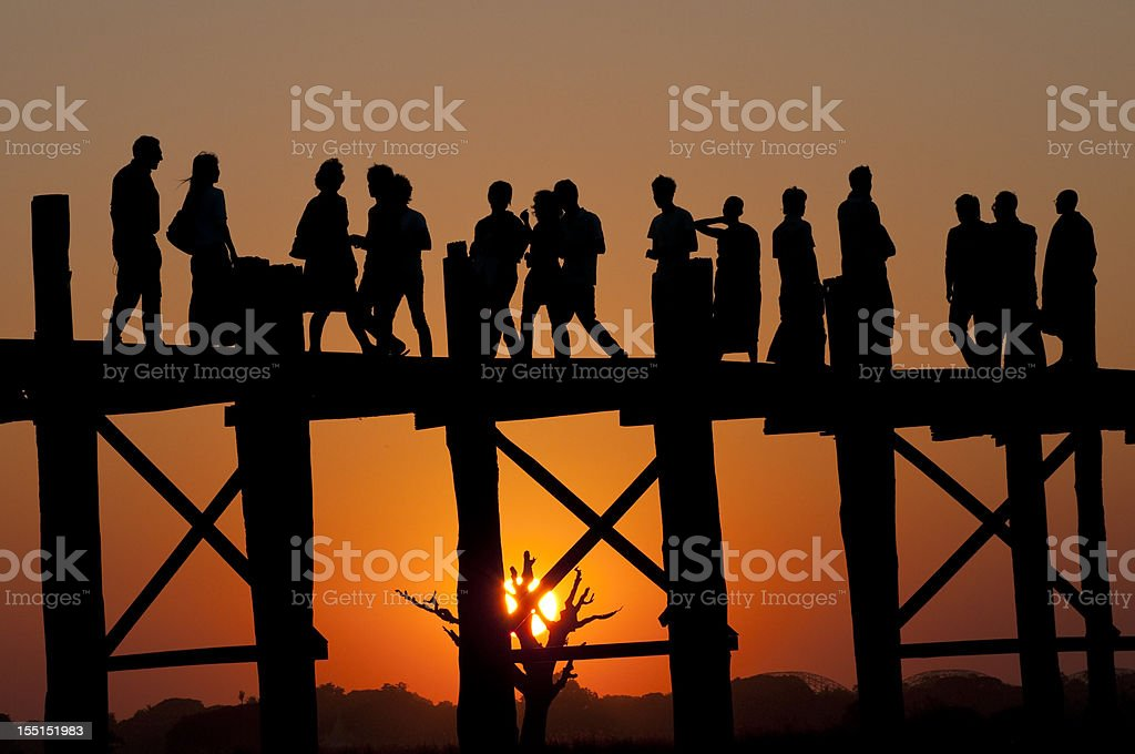 Silhouetted people together at sunset on U Bein Bridge stock photo