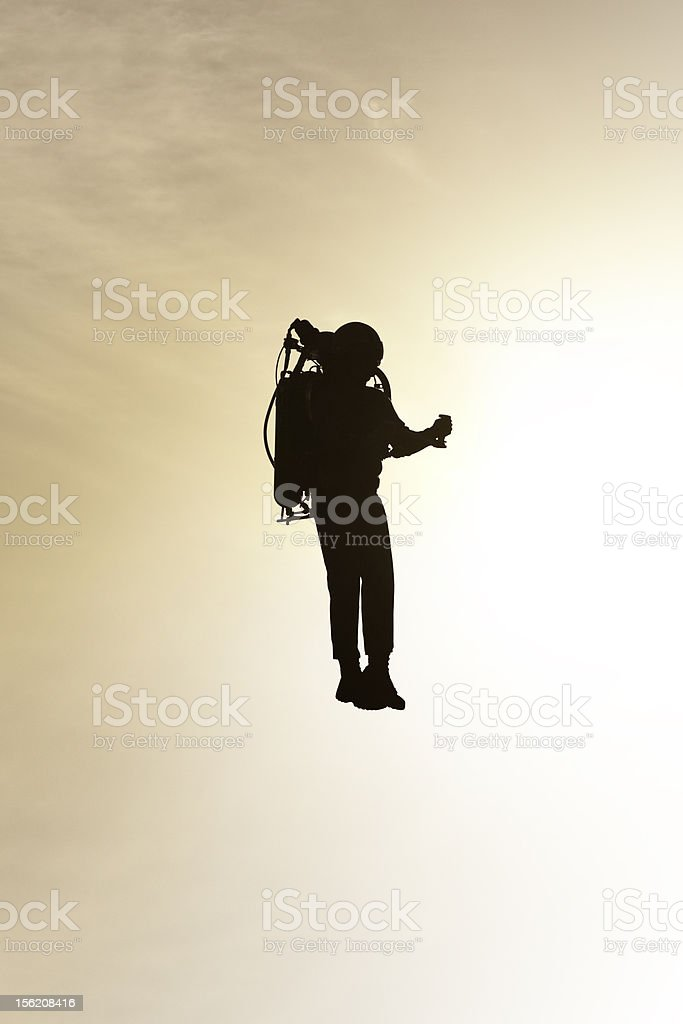 Silhouetted Rocket Jet Pack Man Flying at Sunset stock photo