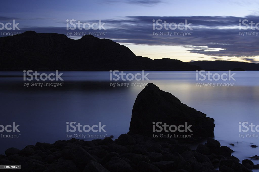 Silhouetted rocks and hills stock photo