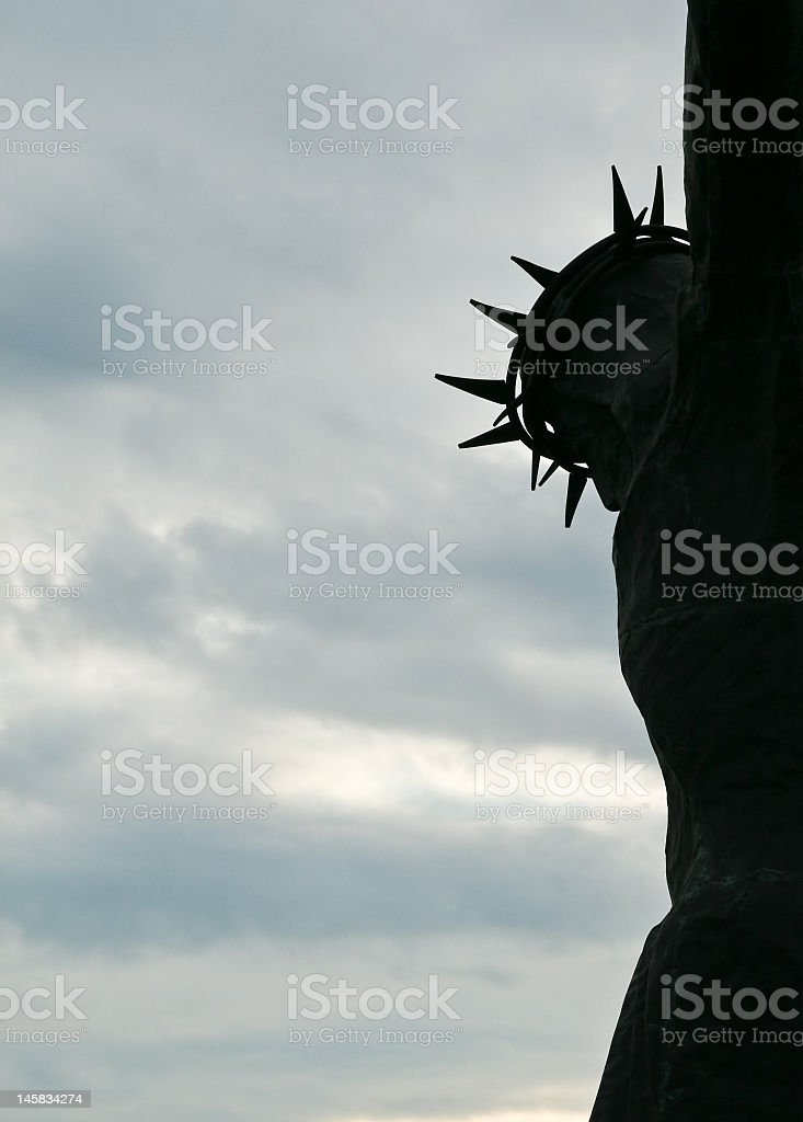 Silhouetted statue of Jesus Christ with a crown of thorns stock photo