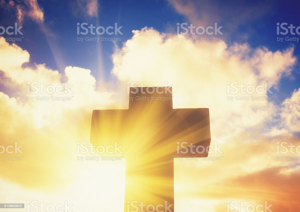 Silhouetted stone cross with sunbeam breaking through clouds stock photo