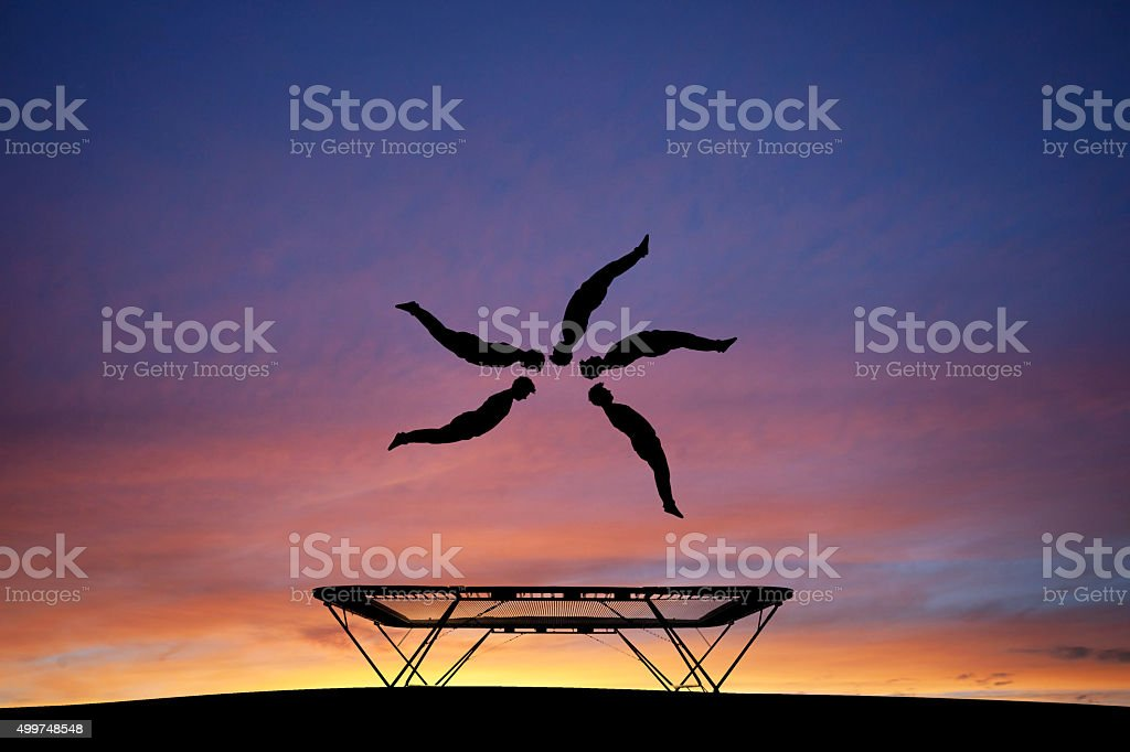 silhouetted trampoline gymnast stock photo