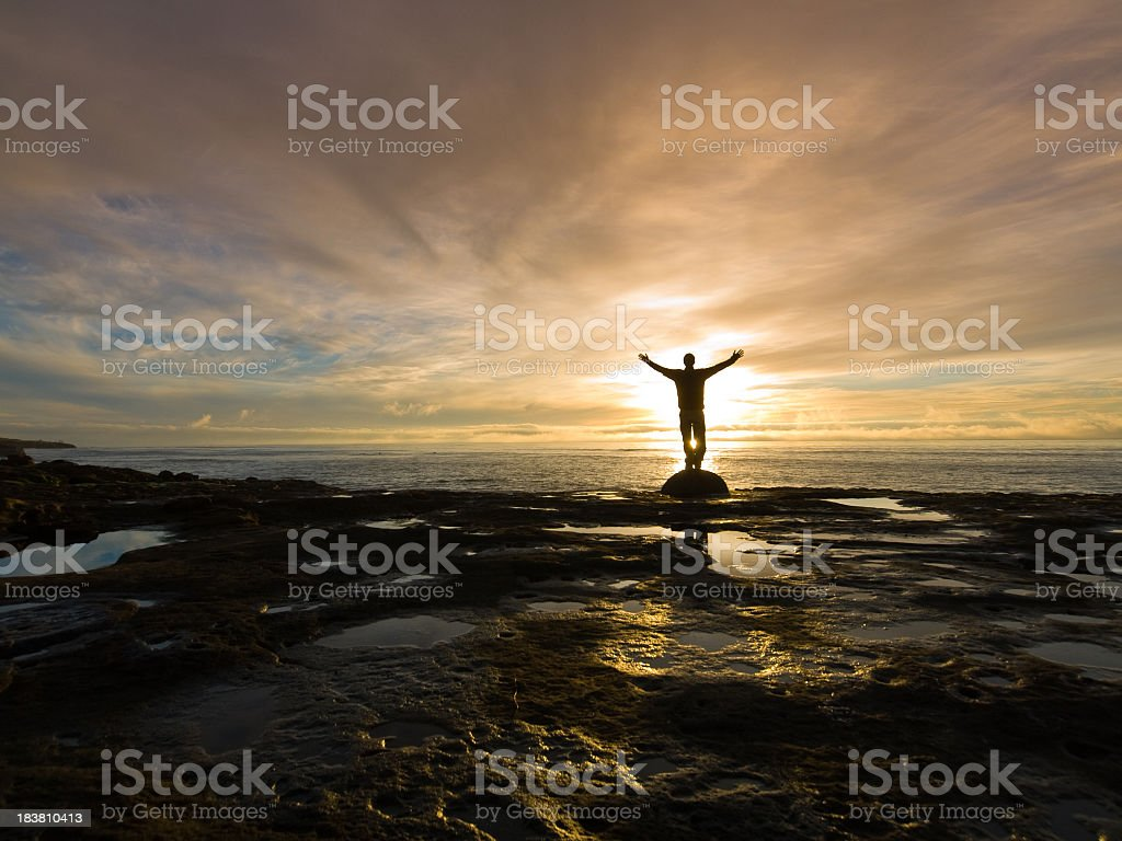 Silhouetted with arms raised on rocky beach at sunrise stock photo