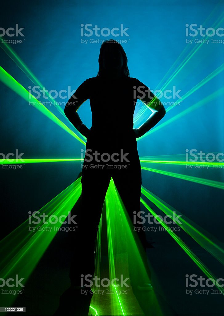 Silhouetted woman against strobed green laser on blue background royalty-free stock photo