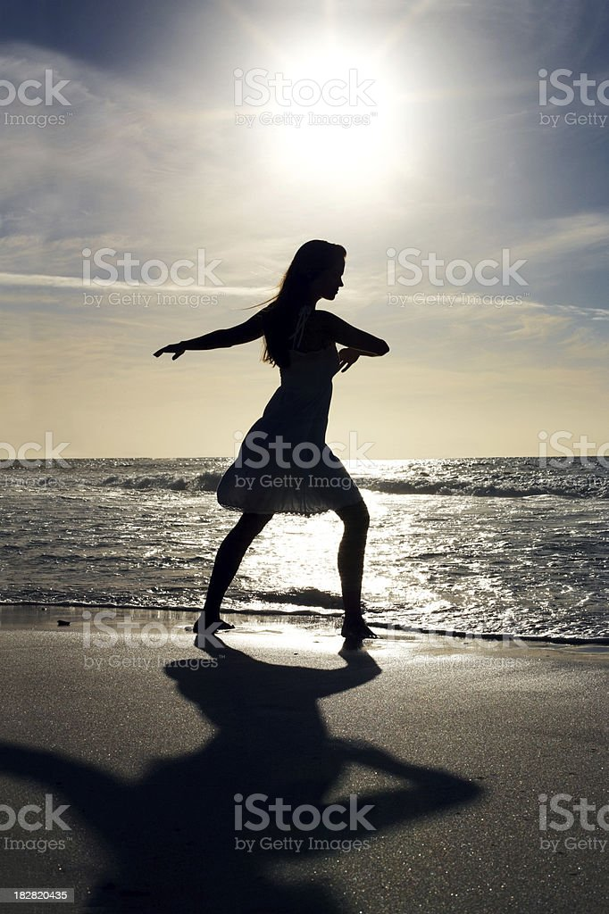 Silhouetted woman dancing on shore at beach royalty-free stock photo