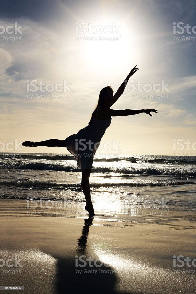 Silhouetted woman exercising on  beach against sunrise royalty-free stock photo