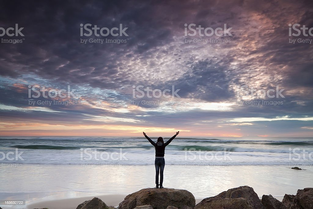Silhouetted woman in front of beach stock photo