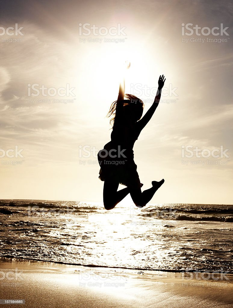 Silhouetted  woman jumping in air by the sea at sunset royalty-free stock photo