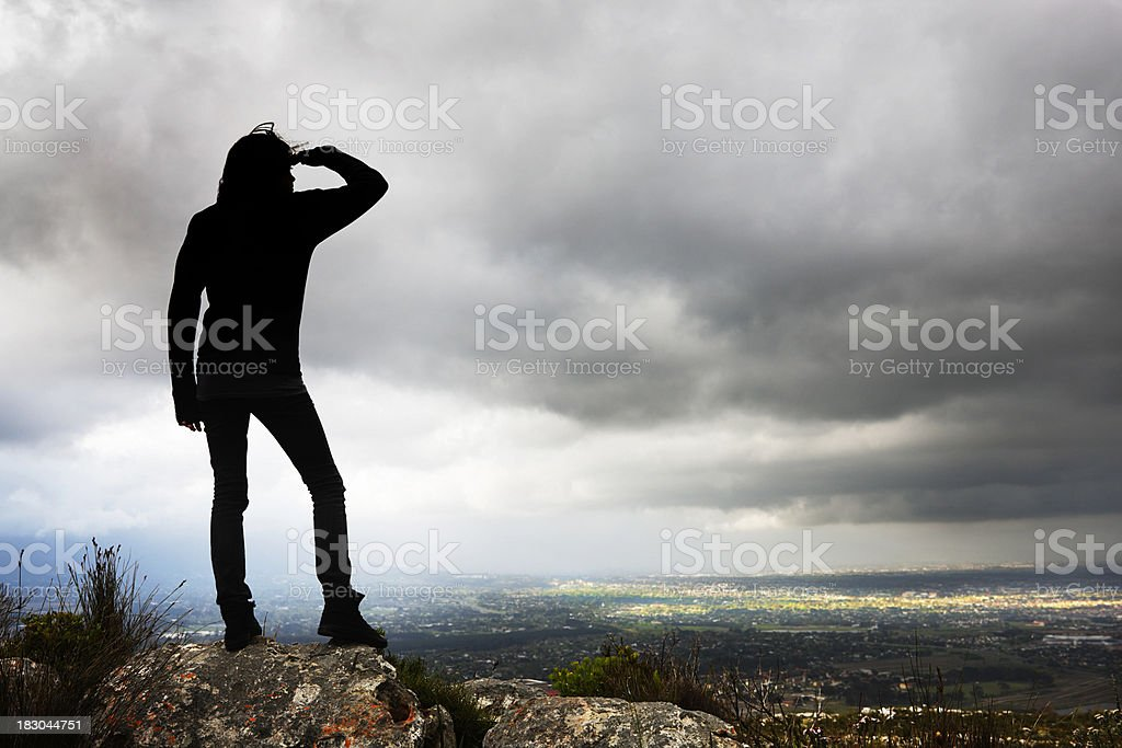 Silhouetted woman looks over stormy landscape towards patch of sunlight stock photo