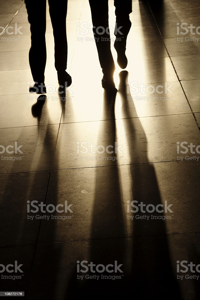 Silhouettes and Shadows of Two Businessman Walking in Corridor stock photo