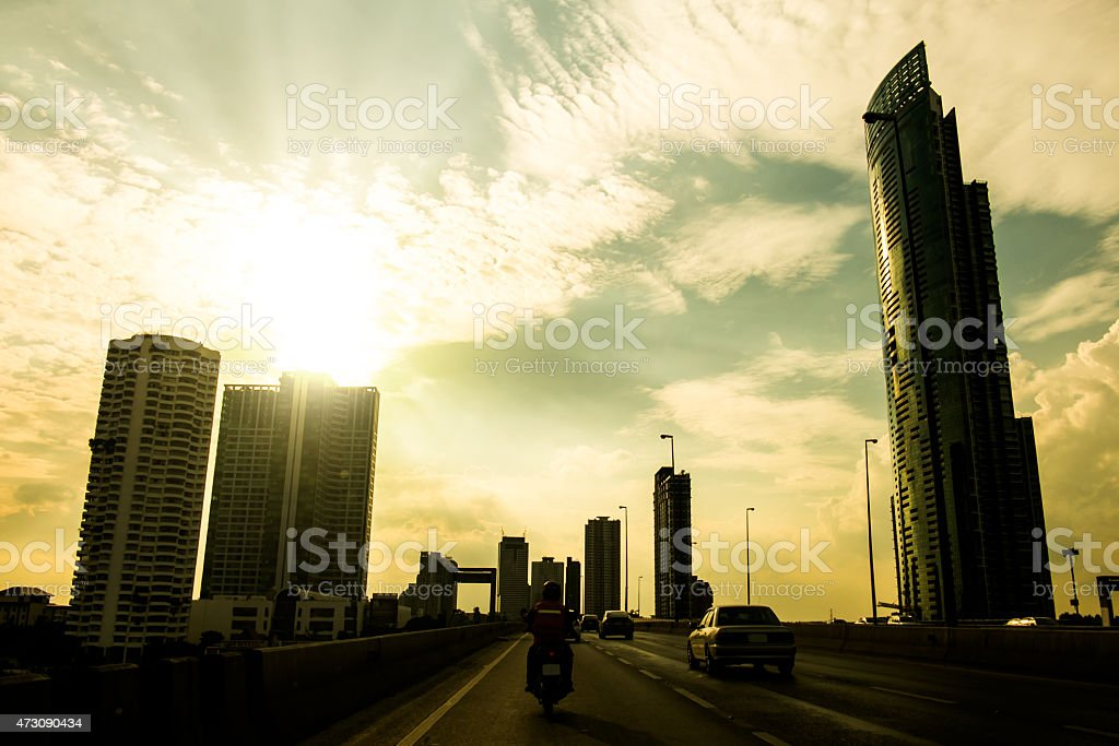 silhouettes city building with sun burst and evening sky stock photo