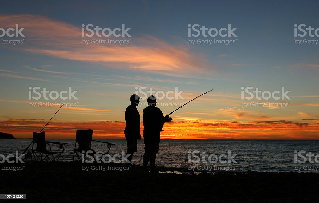 Silhouettes fishing on the beach stock photo