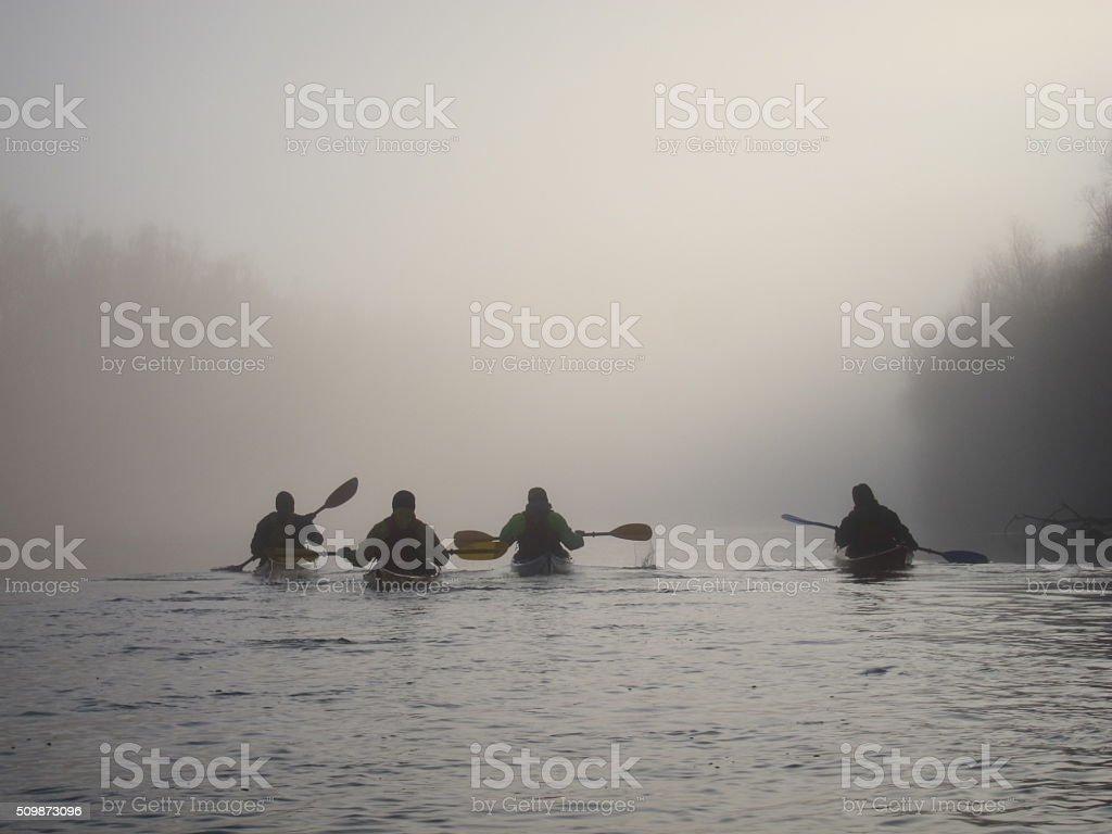 Silhouettes four men in kayak in the foggy Danube river stock photo
