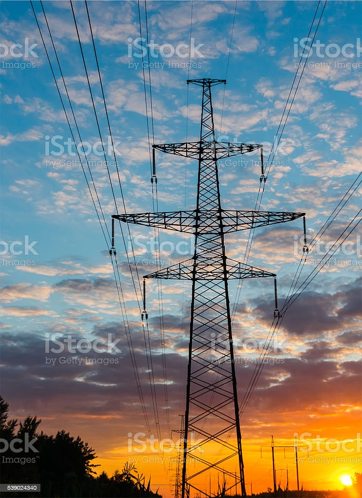 Silhouettes high voltage electric pylon in sunset background stock photo