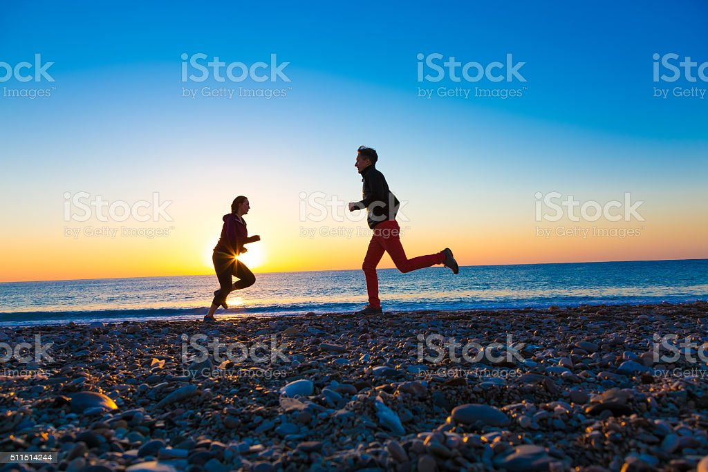Silhouettes Man and Woman jogging along Sea Beach at Sunrise stock photo