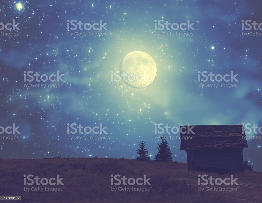 Silhouettes of a countryside with Milky way and Moon stock photo