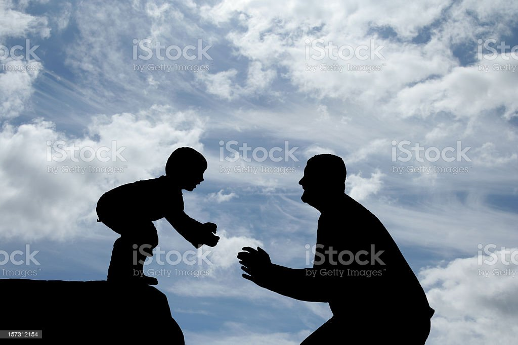 Silhouettes of a father and son playing stock photo