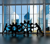 Silhouettes of business partners moving gears inside an office