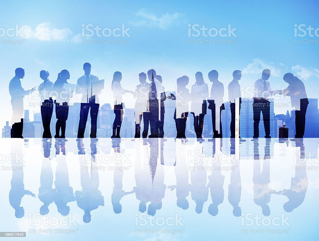 Silhouettes of Business People Communicating in a Cityscape stock photo
