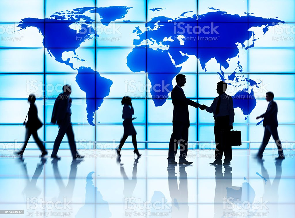Silhouettes of business people greeting against map wall royalty-free stock photo