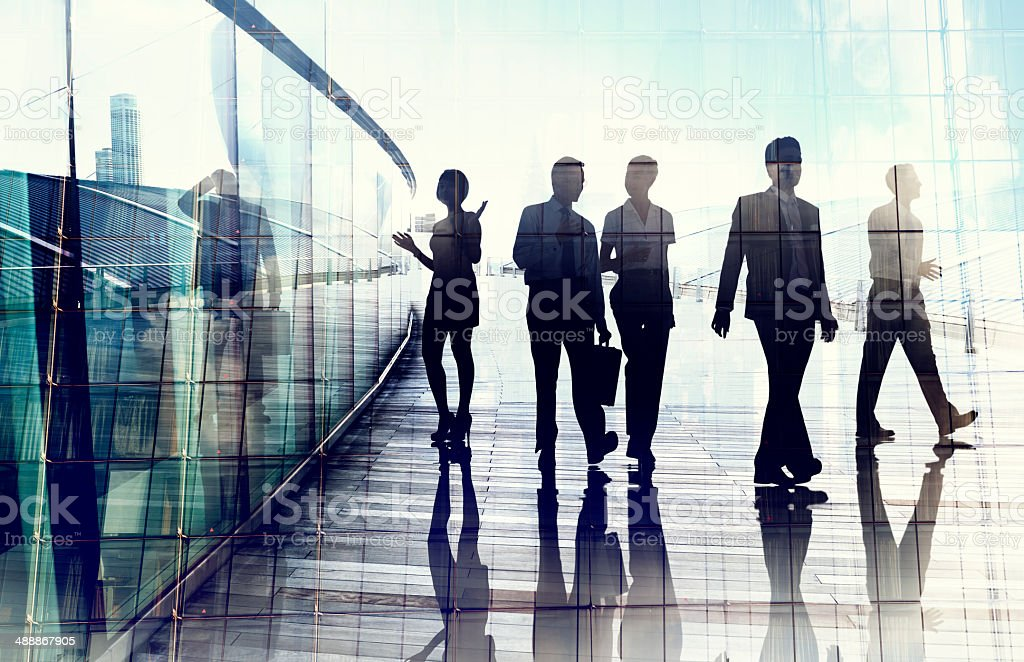 Silhouettes of Business People in Blurred Motion Walking stock photo