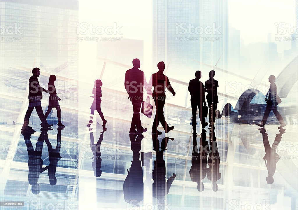 Silhouettes of Business People Walking inside the Office stock photo