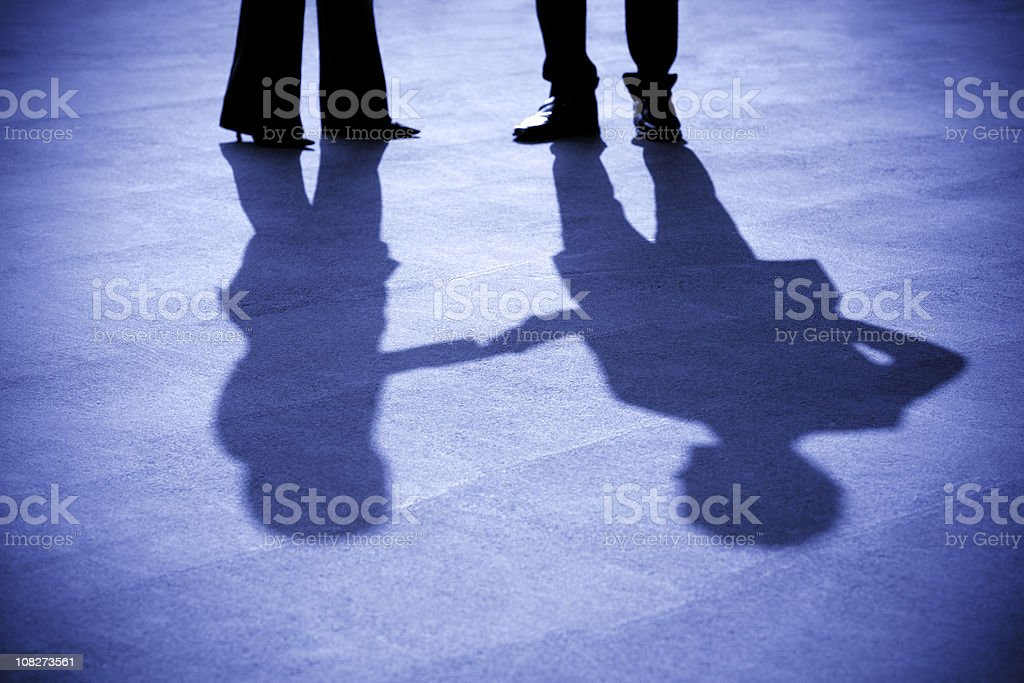 Silhouettes of businesswoman and businessman stock photo