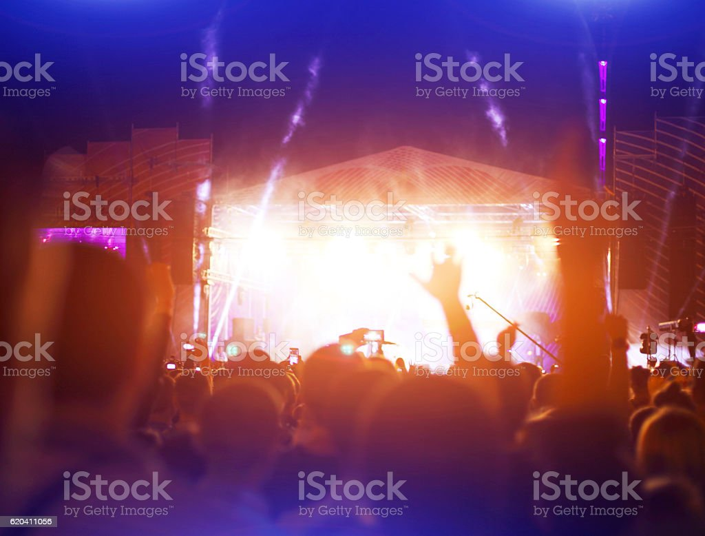 Silhouettes of concert crowd in front bright stage lights stock photo