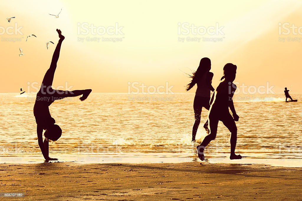 Silhouettes of girls on the beach at sunset stock photo
