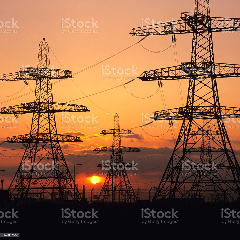 Silhouettes of large electric transmission towers at sunset royalty-free stock photo