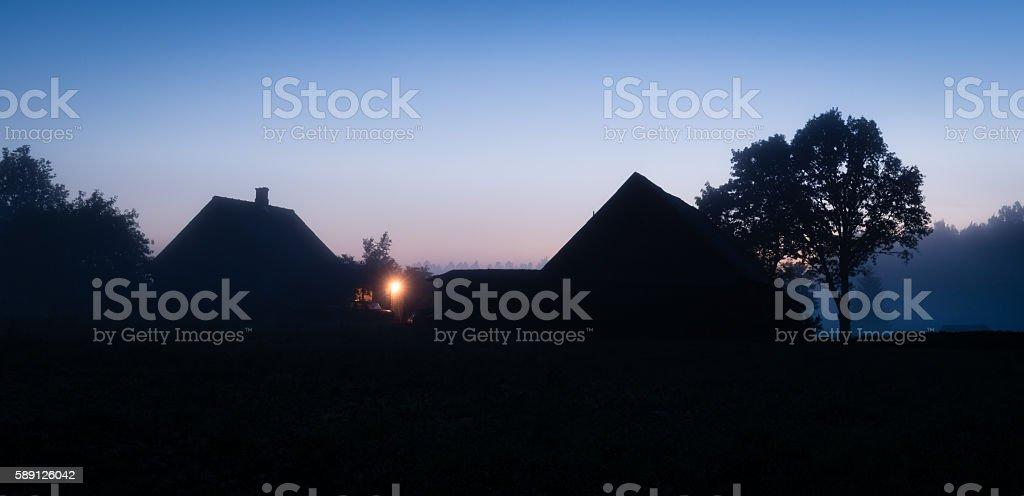 Silhouettes of Latvian farmhouse at sunset stock photo