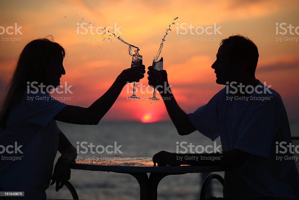Silhouettes of man and woman splash out drink from glass. royalty-free stock photo