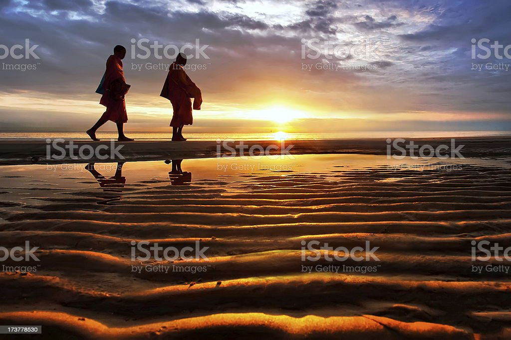 Silhouettes of monks on Hua Hin beach Thailand stock photo