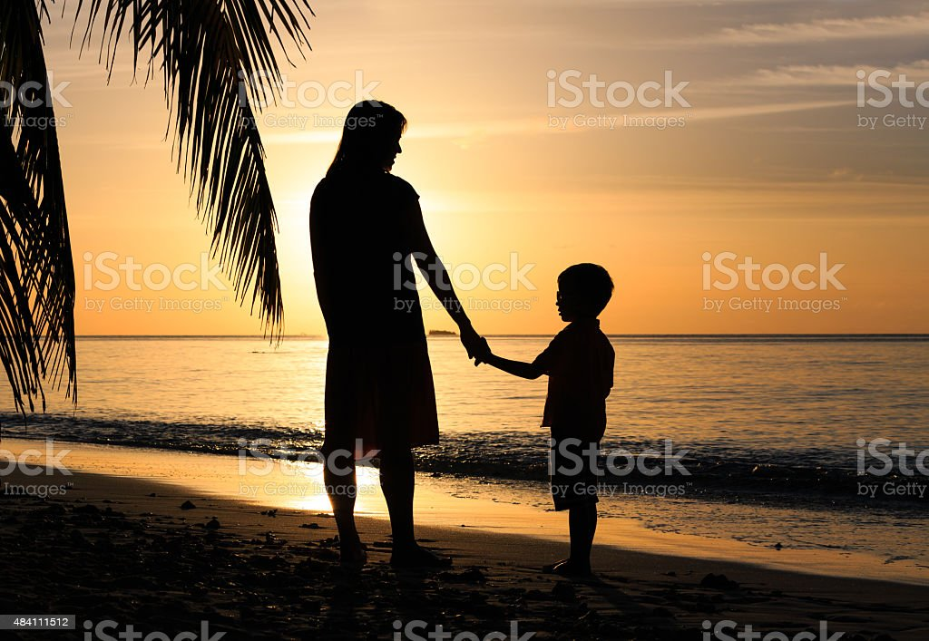 silhouettes of mother and son holding hands at sunset stock photo