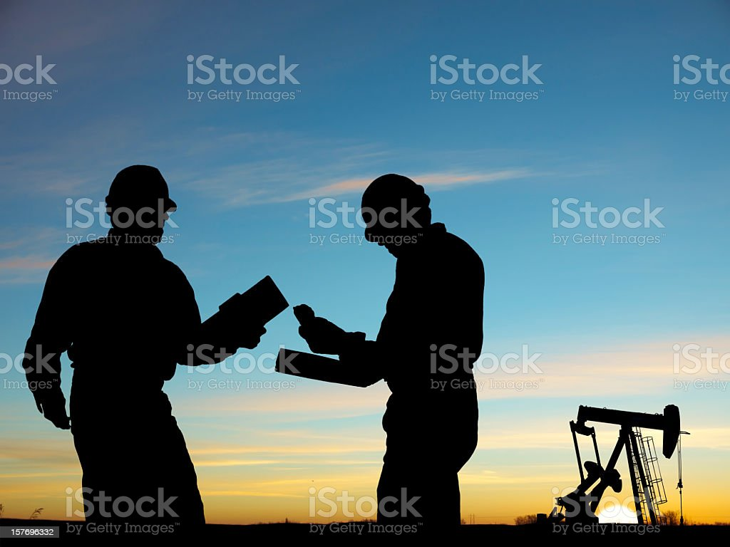 2 silhouettes of oil workers and a pump royalty-free stock photo