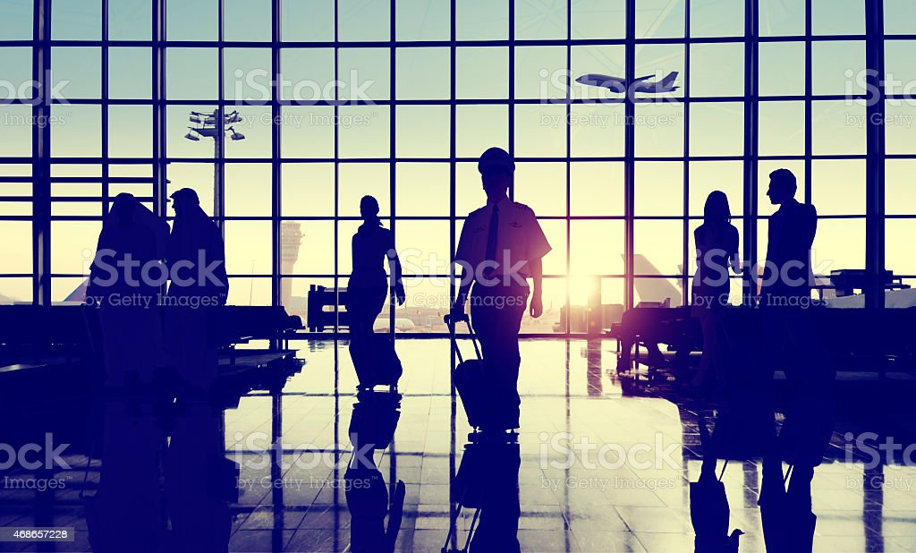 Silhouettes of people at an airport for business travel stock photo