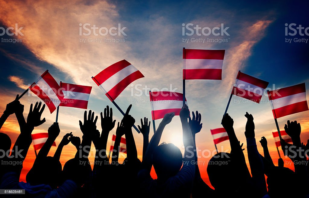 Silhouettes of People Holding Flag of Austria stock photo