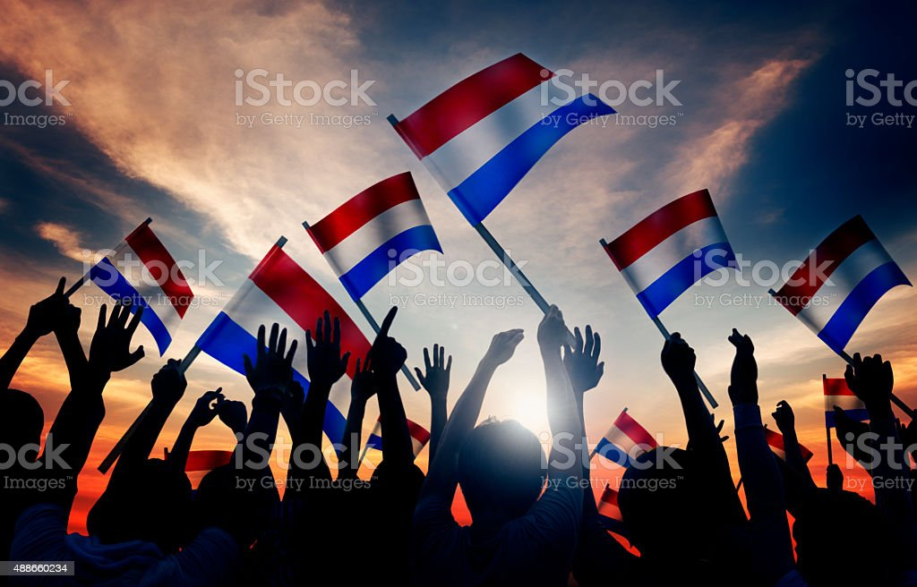 Silhouettes of People Holding Flag of Netherlands stock photo
