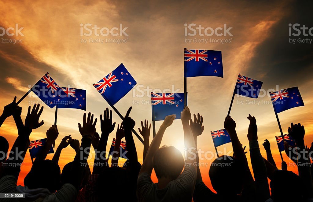 Silhouettes of People Holding Flag of New Zealand stock photo