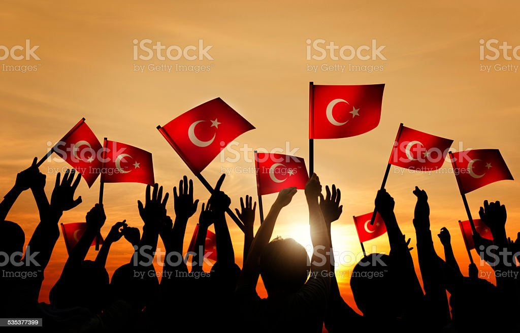 Silhouettes of People Holding the Flag of Turkey stock photo