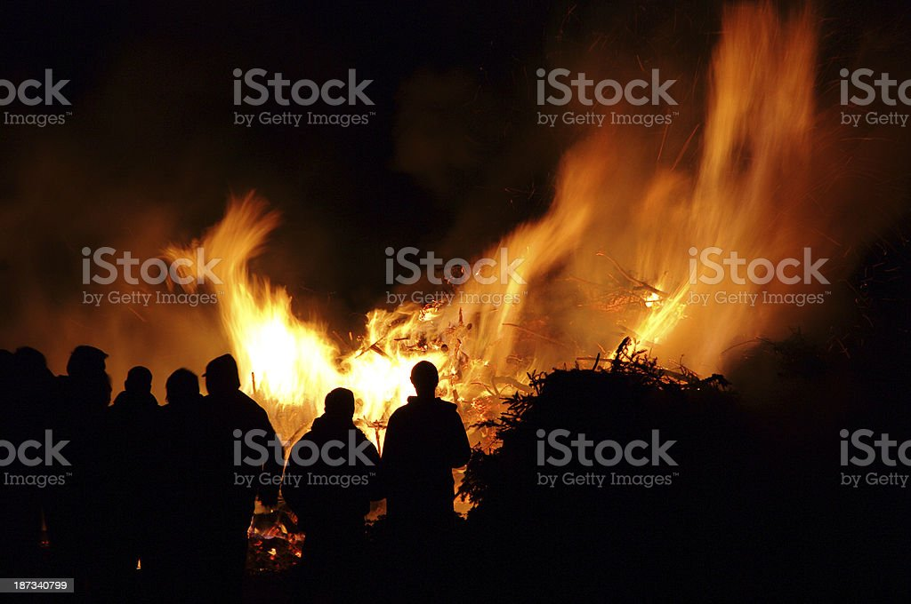 Silhouettes of people in front of a Walpurgis Night bonfire stock photo