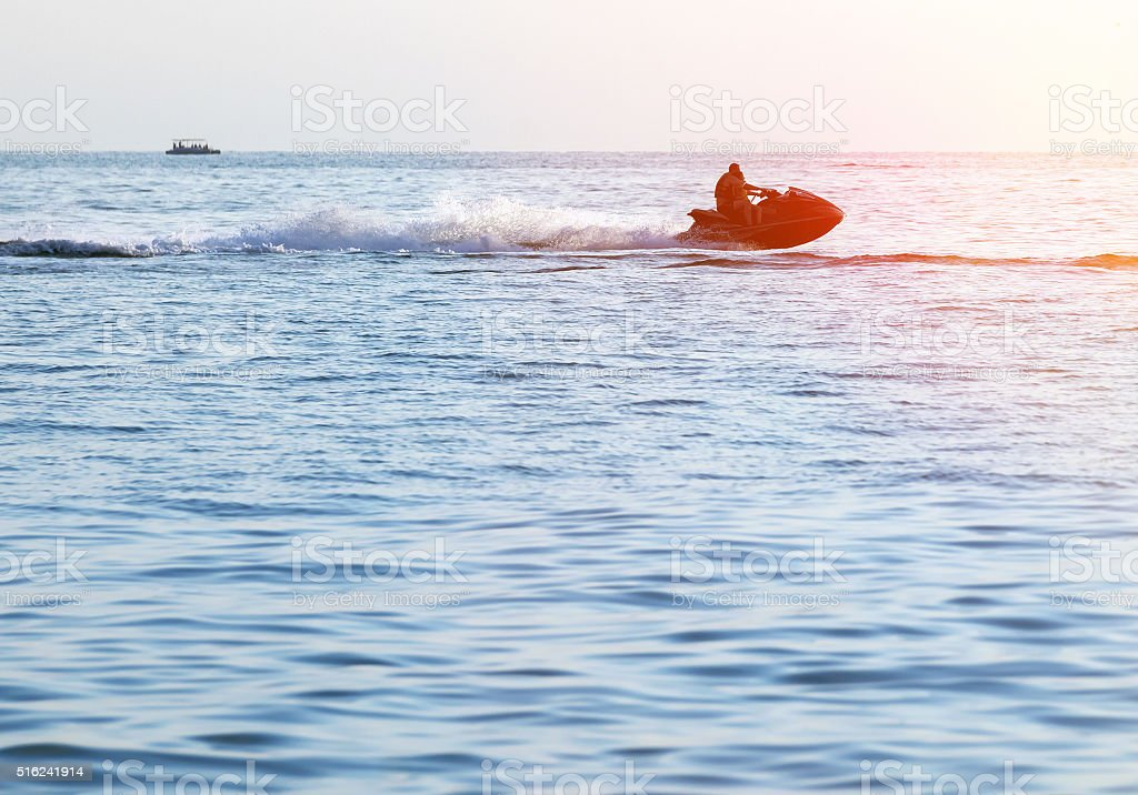 Silhouettes of people in motion on jetski stock photo