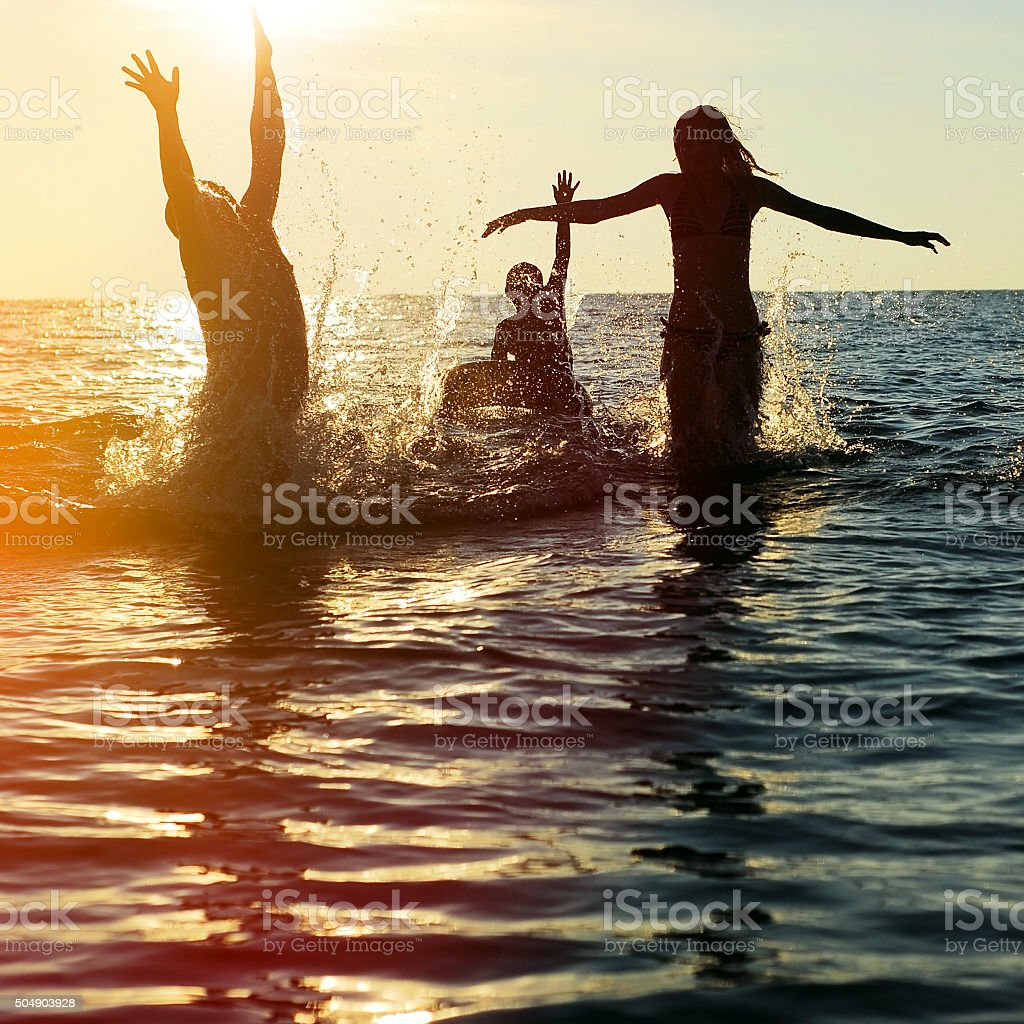 Silhouettes of people jumping in ocean stock photo