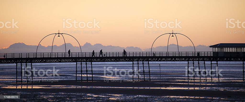 Silhouettes of people walking at sunset down Pier. royalty-free stock photo