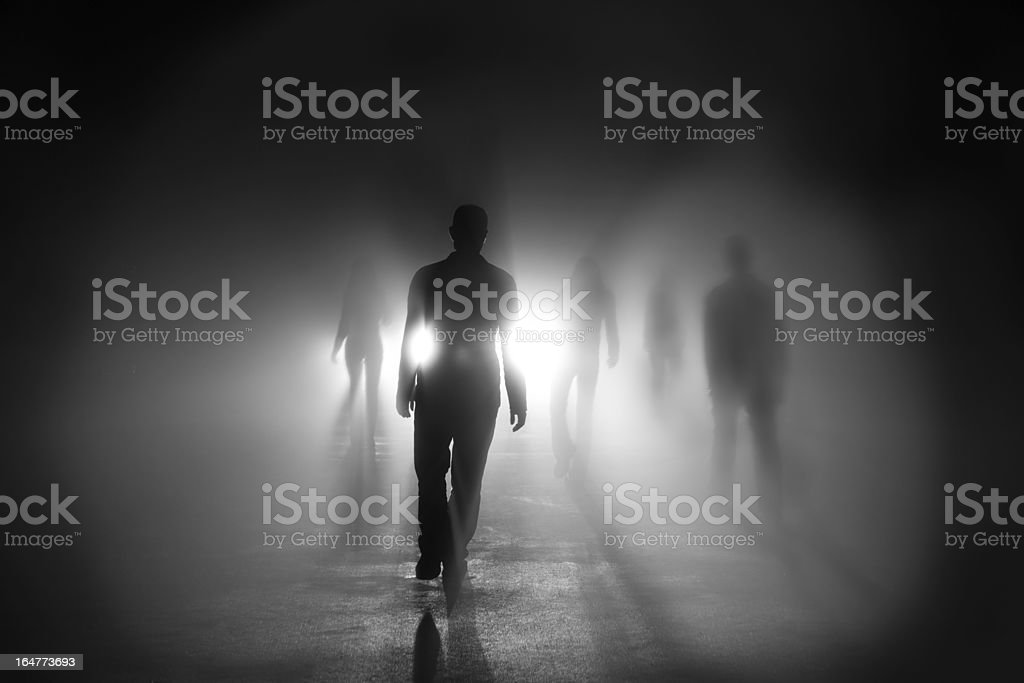 Silhouettes of people walking into light stock photo