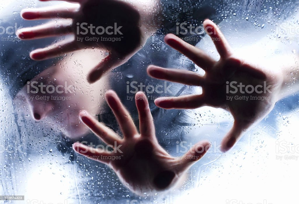 Silhouettes of person behind wet glass stock photo