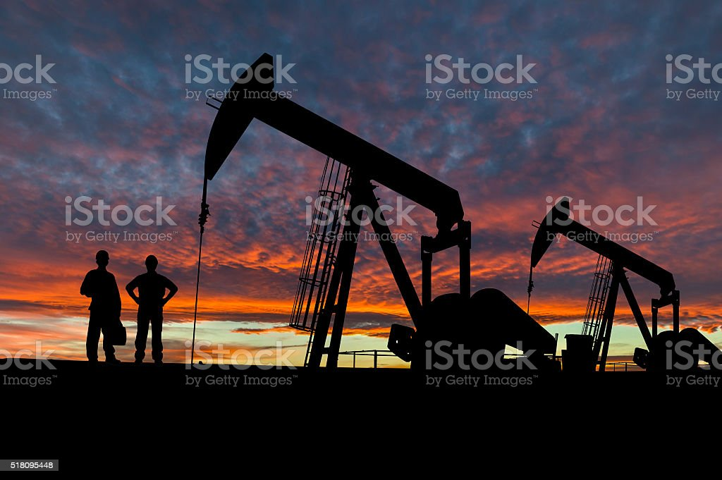 Silhouettes of Pumpjacks and Oil Workers stock photo