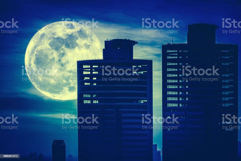 Silhouettes of skyscrapers different construction with supermoon stock photo