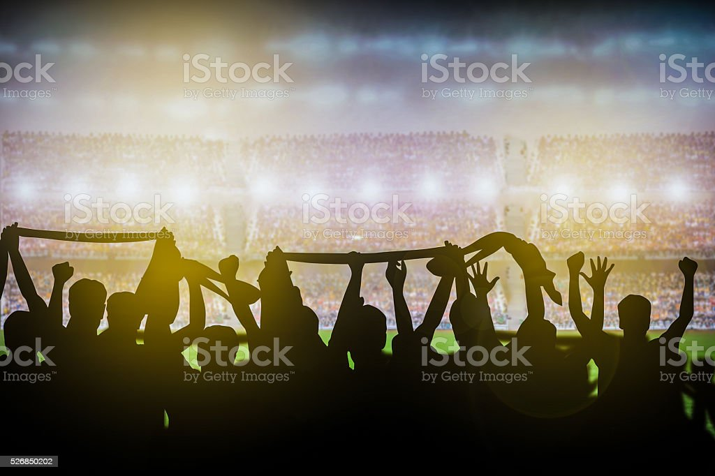 Silhouettes of soccer or rugby supporters in the stadium stock photo